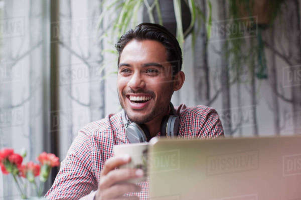 Man laughing and drinking coffee at laptop in cafe Royalty-free stock photo