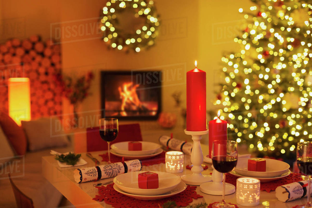 Christmas Crackers.Ambient Candles And Christmas Crackers On Dinner Table In Living Room With Fireplace And Christmas Tree Stock Photo