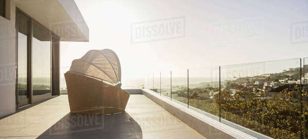 Covered lounge chair on sunny luxury sunset balcony Royalty-free stock photo