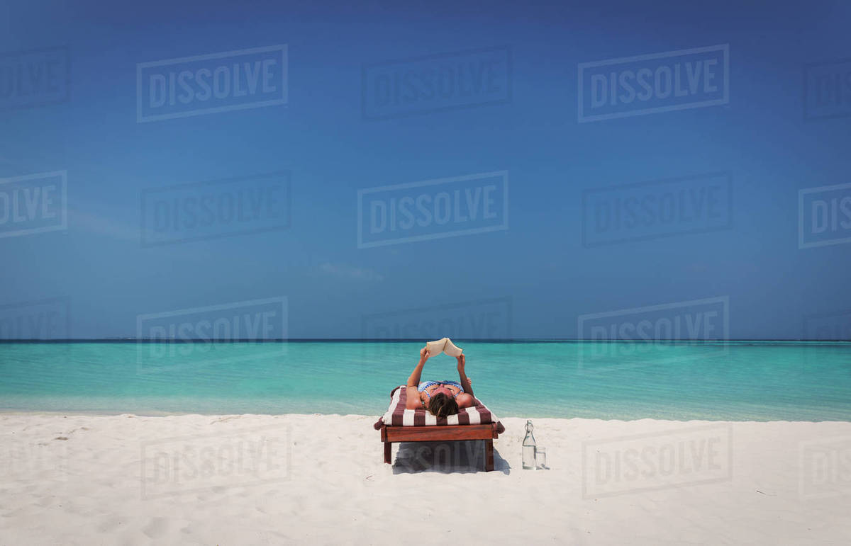 Woman Relaxing Laying And Reading Book On Lounge Chair Sunny Tropical Beach