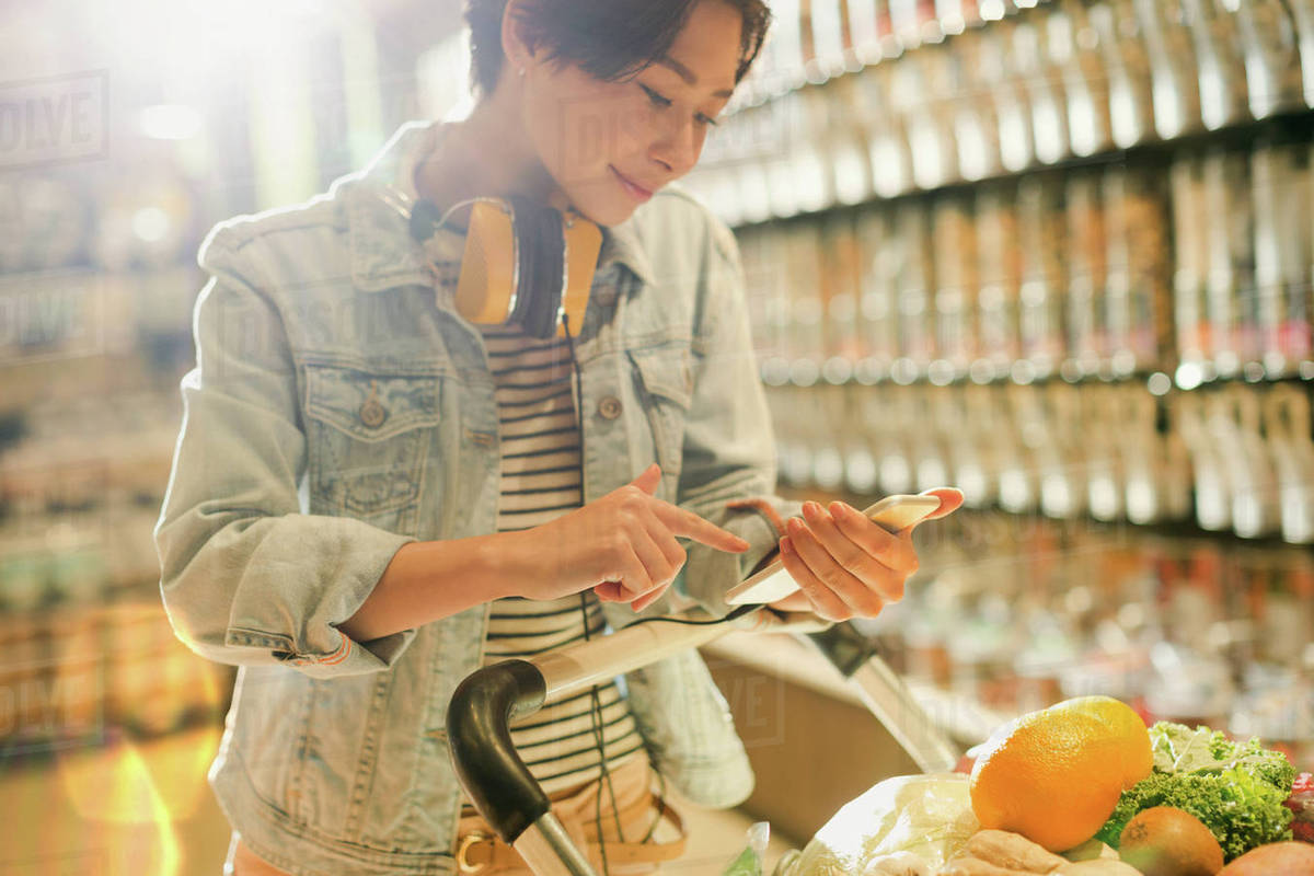 Young woman with headphones using cell phone in grocery store market Royalty-free stock photo