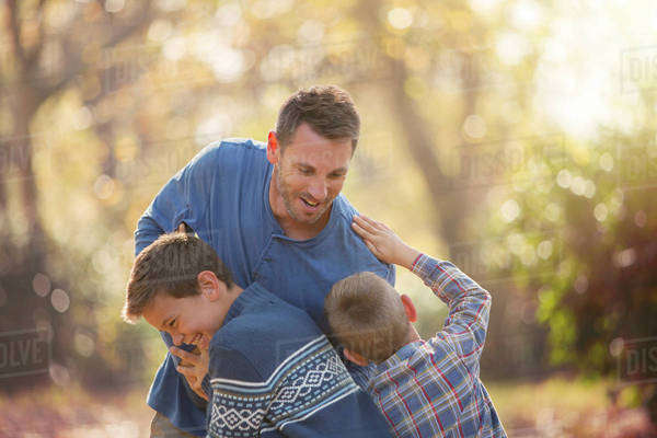 Playful father and sons rough housing outdoors Royalty-free stock photo