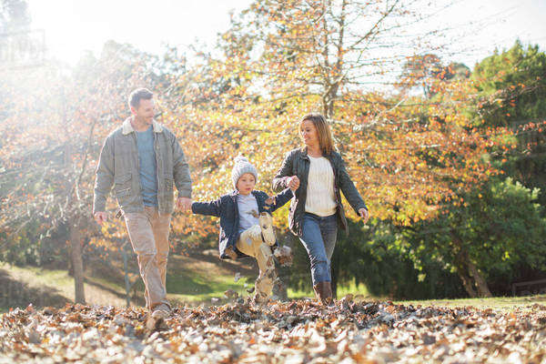 Family holding hands and walking in autumn leaves Royalty-free stock photo