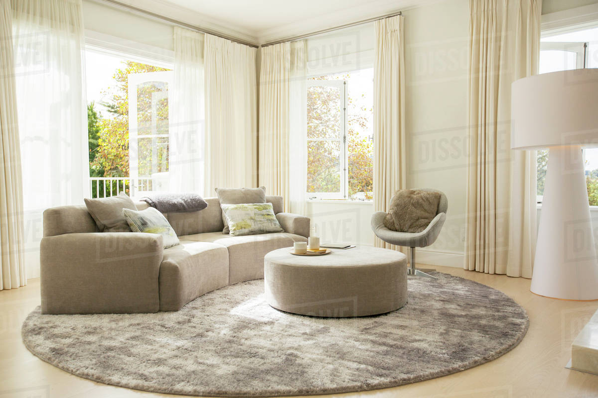 Round carpet under sofa and ottoman in living room stock photo