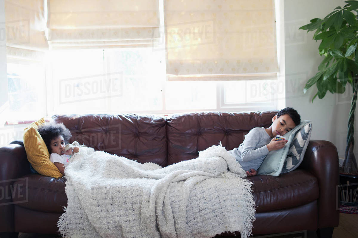 Brother and sister relaxing, watching TV on living room sofa stock photo