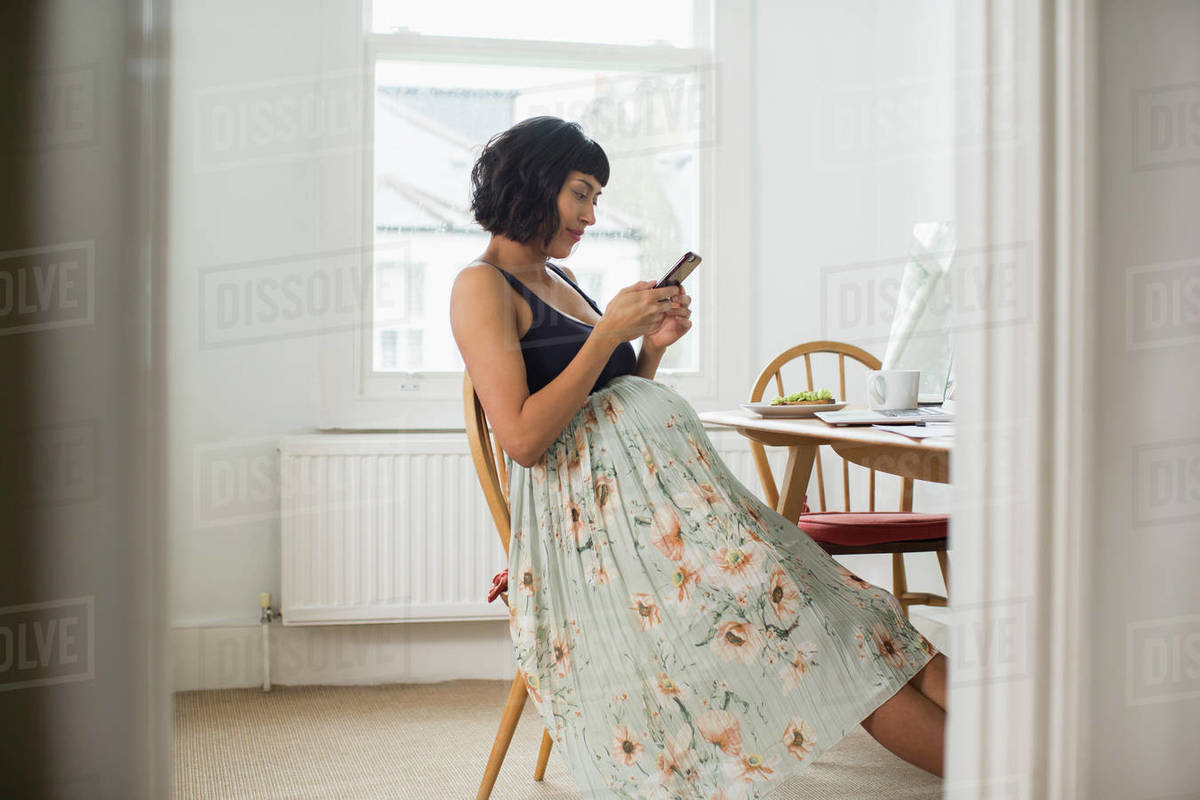 Pregnant woman in floral dress using smart phone at table Royalty-free stock photo