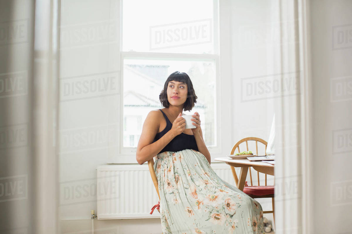 Thoughtful pregnant woman drinking tea in apartment Royalty-free stock photo
