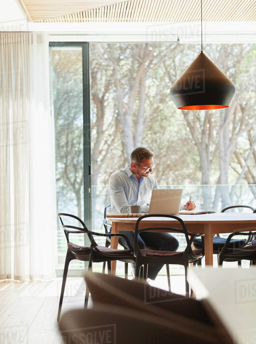 Businessman working at laptop and taking notes, working from home Royalty-free stock photo