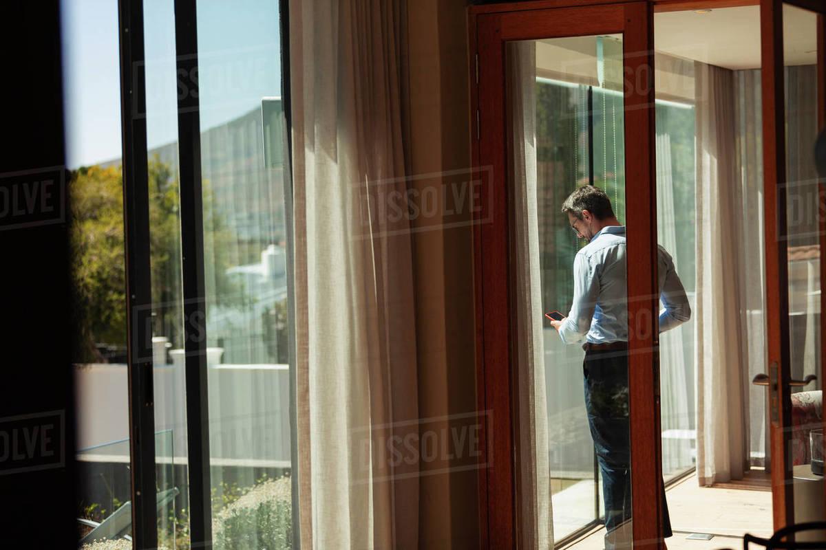 Businessman using smart phone at sunny window Royalty-free stock photo