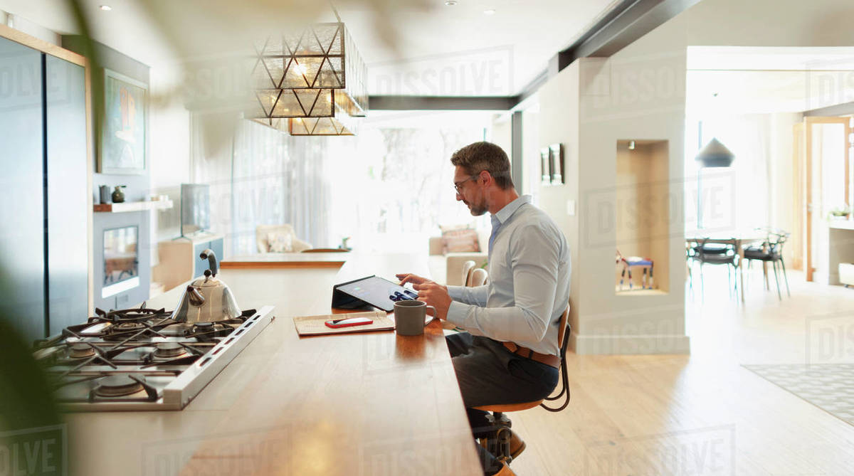 Businessman at digital tablet working from home in modern kitchen Royalty-free stock photo