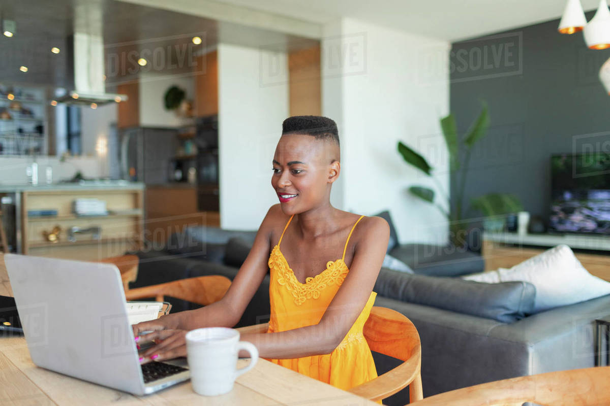 Young woman using laptop, working from home at dining table Royalty-free stock photo