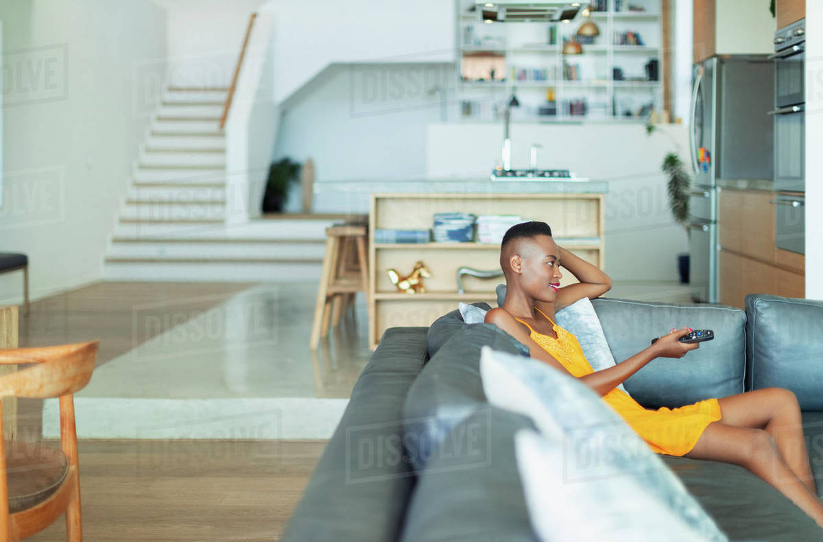 Young woman with remote control watching TV on living room sofa Royalty-free stock photo