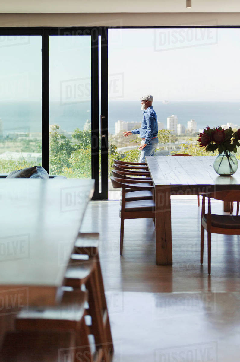 Man standing on sunny, modern patio with ocean view Royalty-free stock photo