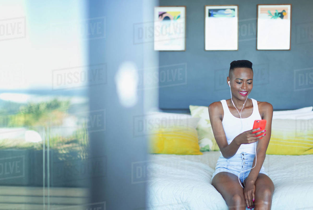 Young woman listening to music with headphones and mp3 player on bed Royalty-free stock photo