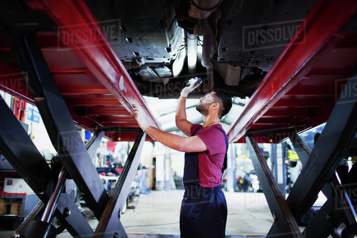 Male mechanic with flashlight under car in auto repair shop Royalty-free stock photo