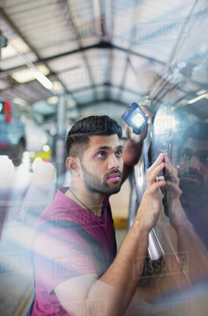 Focused male mechanic with flashlight examining scratches on car in auto repair shop Royalty-free stock photo