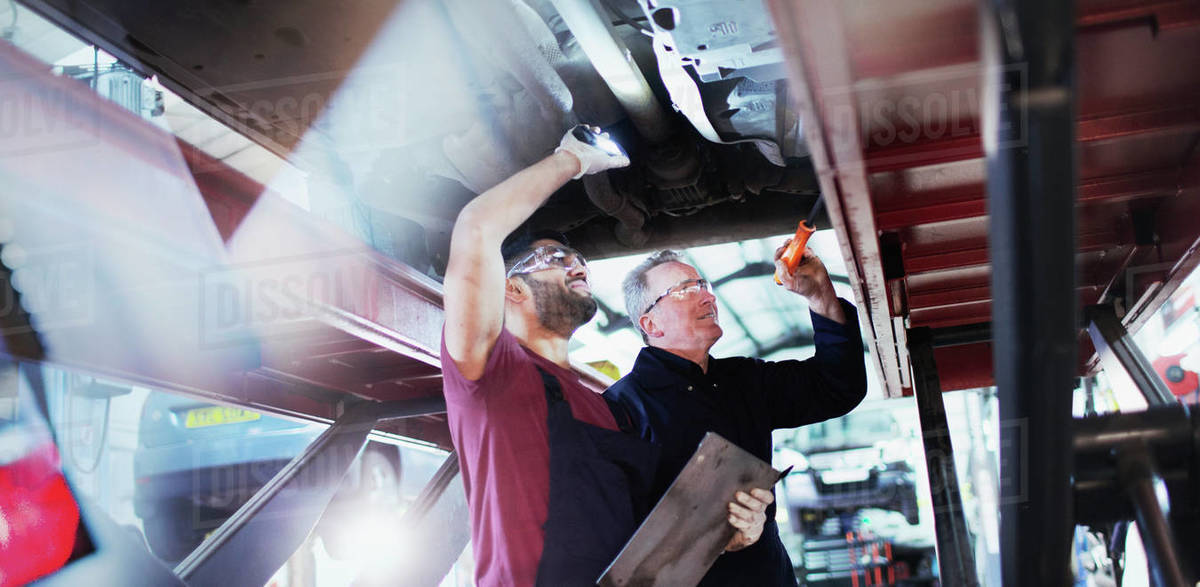 Male mechanics with flashlights working under car in auto repair shop Royalty-free stock photo