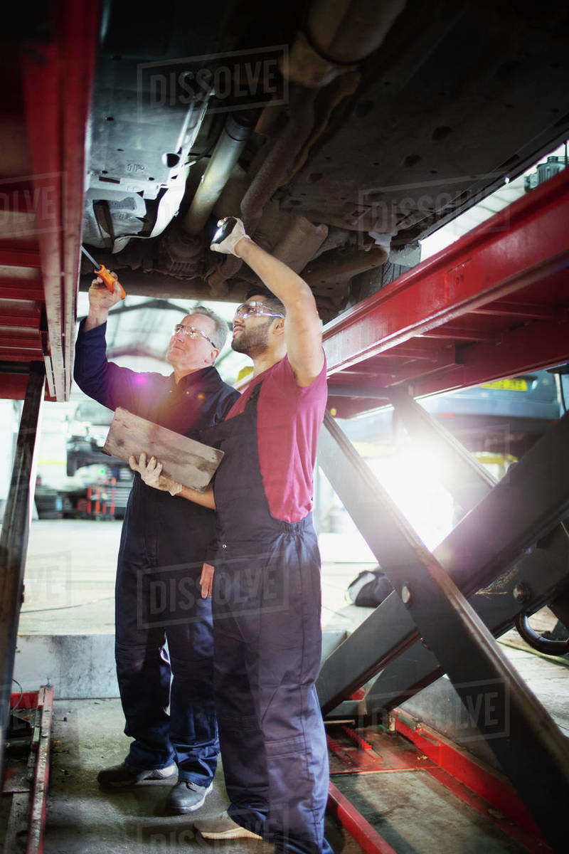 Male mechanics working under car in auto repair shop Royalty-free stock photo
