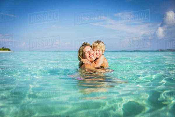 Enthusiastic mother hugging son in tropical ocean Royalty-free stock photo