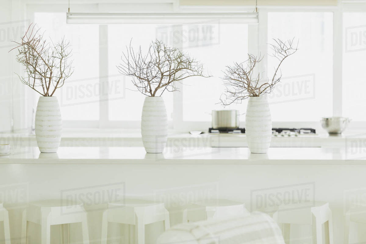 Modern White Dining Table With White Vases And Branches Stock