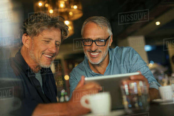 Men using digital tablet at restaurant table Royalty-free stock photo