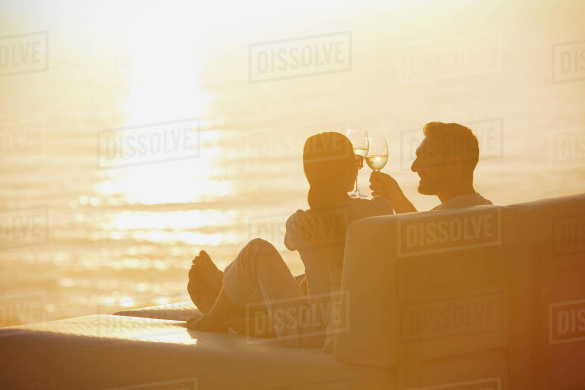 Silhouette couple toasting wine glasses on lounge chair with sunset ocean view & Silhouette couple toasting wine glasses on lounge chair with sunset ...