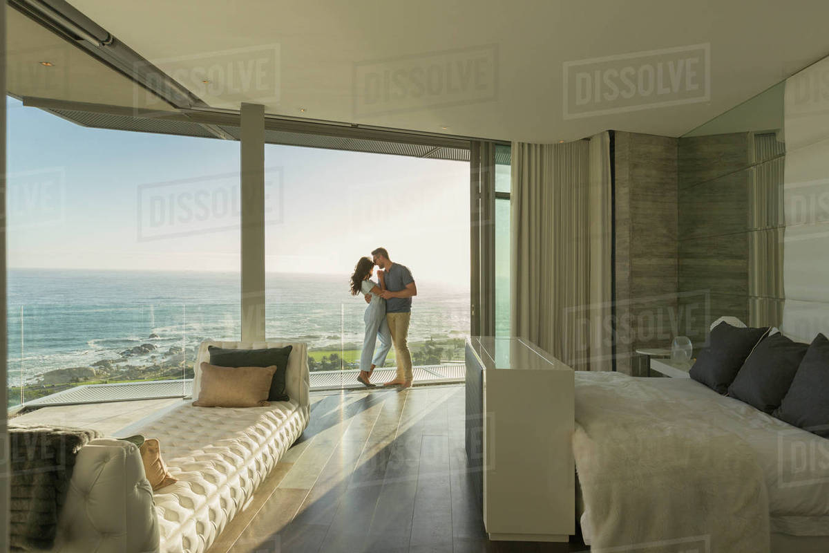 Affectionate Couple Hugging On Modern Luxury Home Showcase Bedroom Balcony  With Ocean View