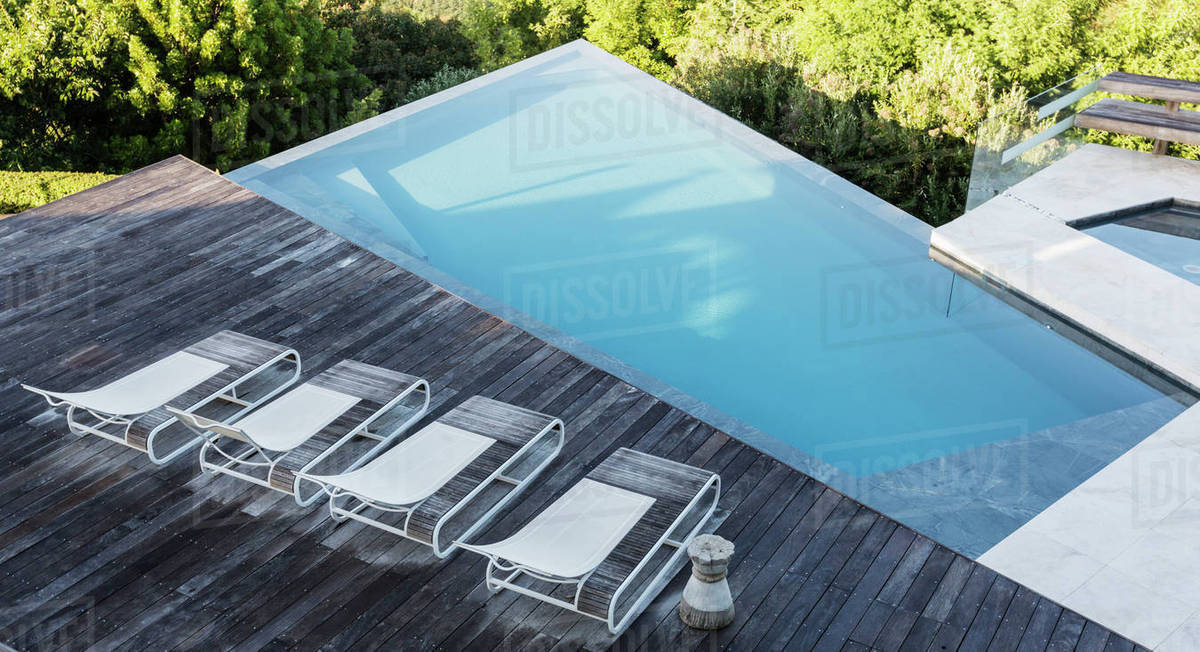 Modern, luxury deck with lounge chairs and swimming pool - Stock ...