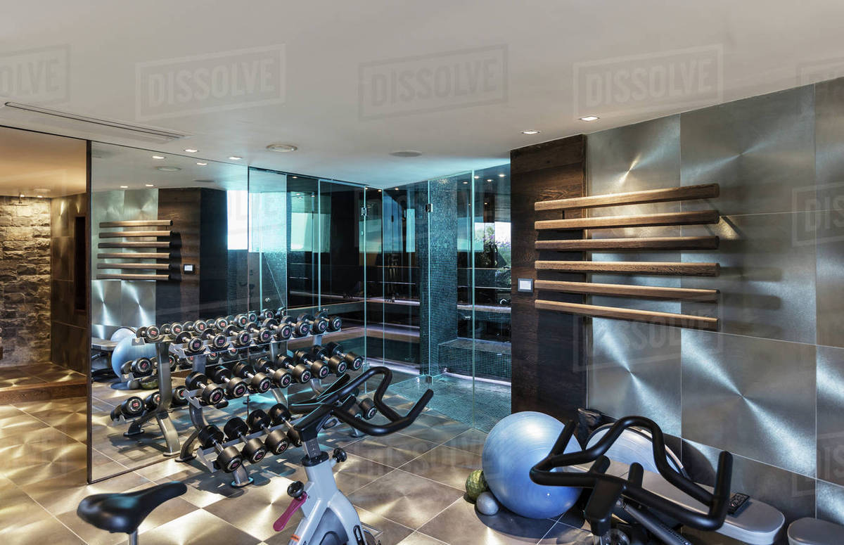 Gym with equipment in modern luxury home showcase interior stock