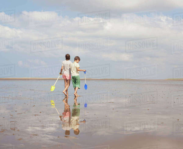 Brother and sister walking with shovels in wet sand on sunny summer beach Royalty-free stock photo