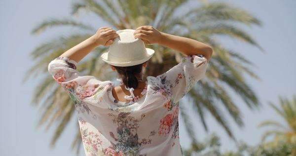 Rear view close-up of woman on vacation wearing floral blouse and white hat standing on tropical palm tree beach with, open arms in celebratory gesture Royalty-free stock video
