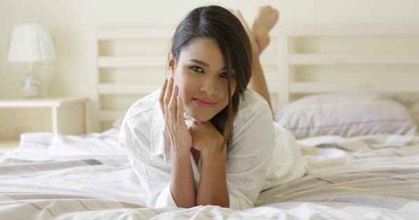 741f2b512c Sexy pretty barefoot young woman in fresh white sleepwear lying on her  stomach on her bed