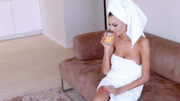 Beautiful young woman enjoying a relaxing morning sitting wrapped in clean white towels drinking a fresh orange juice Royalty-free stock video