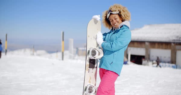 ece76ce7e3 Attractive young woman posing at a winter ski resort in her ski clothes  holding her snowboard