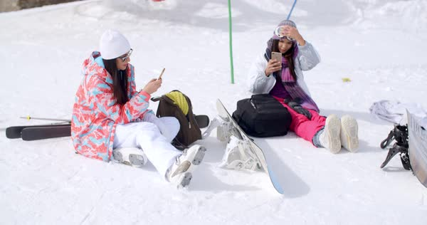 21eb9e1725 Two attractive young female friends relaxing with their snowboards sitting in  the snow in their ski