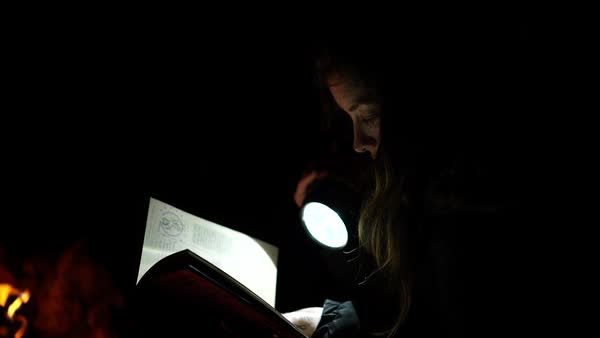 Medium shot of a woman reading a book with flashlight Royalty-free stock video