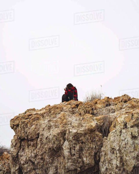 Woman taking pictures on cliff during winter Royalty-free stock photo