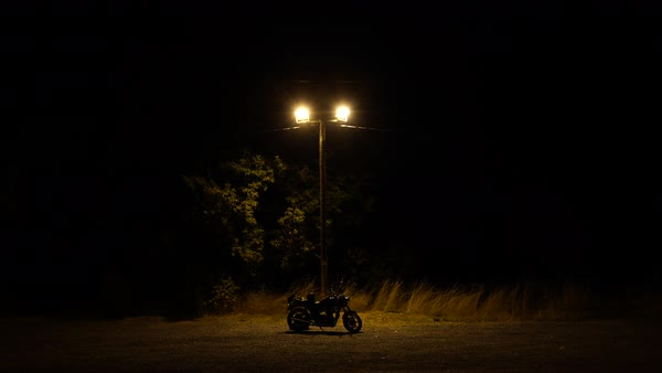 Wide shot of a motorcycle and a streetlight while cars drive away Royalty-free stock video