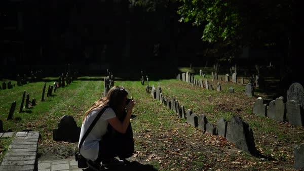 Hand-held shot of a woman photographing tombstones Royalty-free stock video