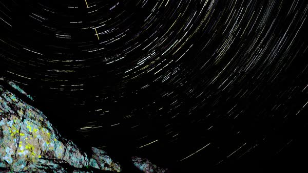 Star trails galaxy spins behind the rock. Timelapse. Royalty-free stock video