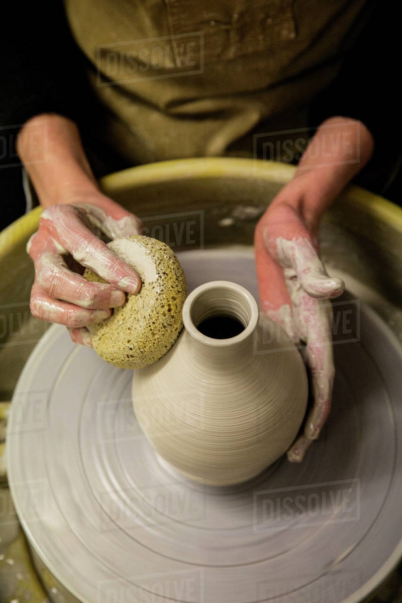 Close Up Of Potter Wearing Apron Working On Pottery Wheel Shaping Clay Vase Stock Photo Dissolve