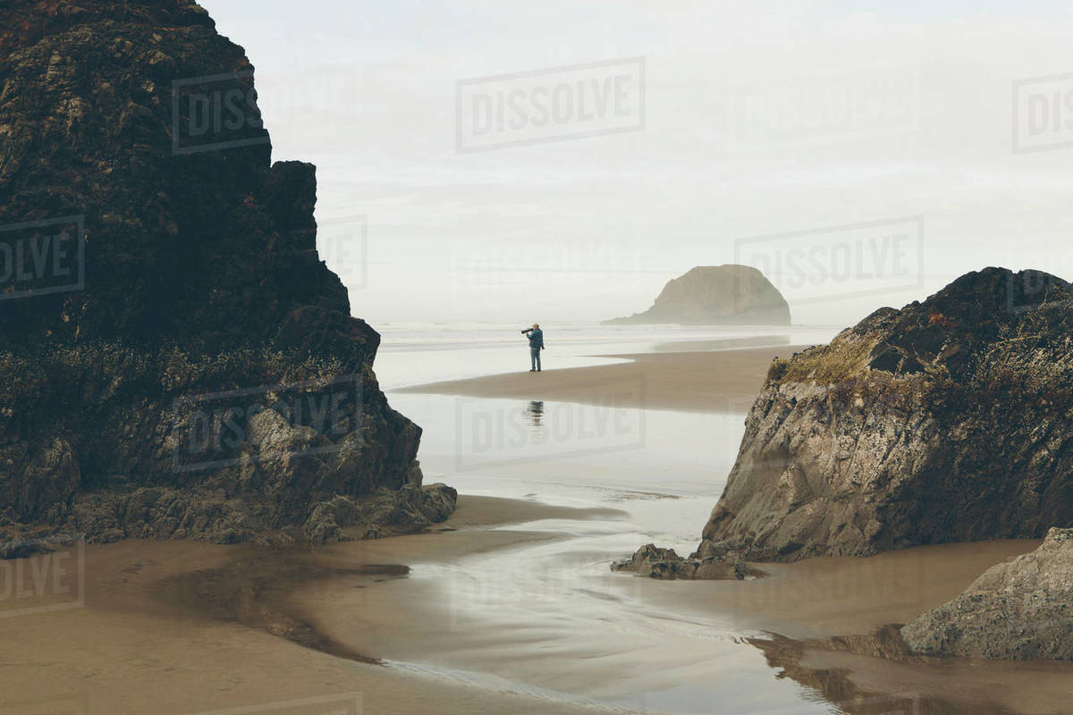 Man Taking Photos On Beach At Low Tide Arcadia State Park Oregon