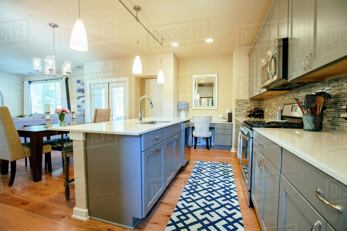 Modern Home Kitchen Diner With Green Grey Fitted Units A Kitchen Island And Blue Floor Rug Stock Photo Dissolve