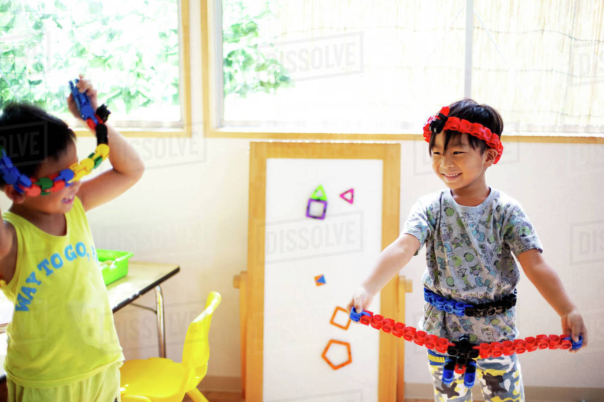 Two Smiling Children Playing With Toys In A Japanese Preschool