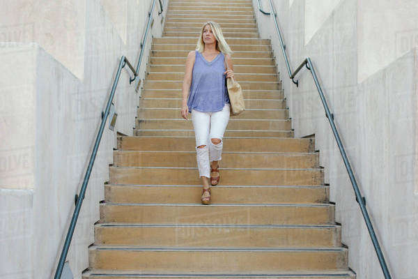 Blond woman walking down a staircase. Royalty-free stock photo