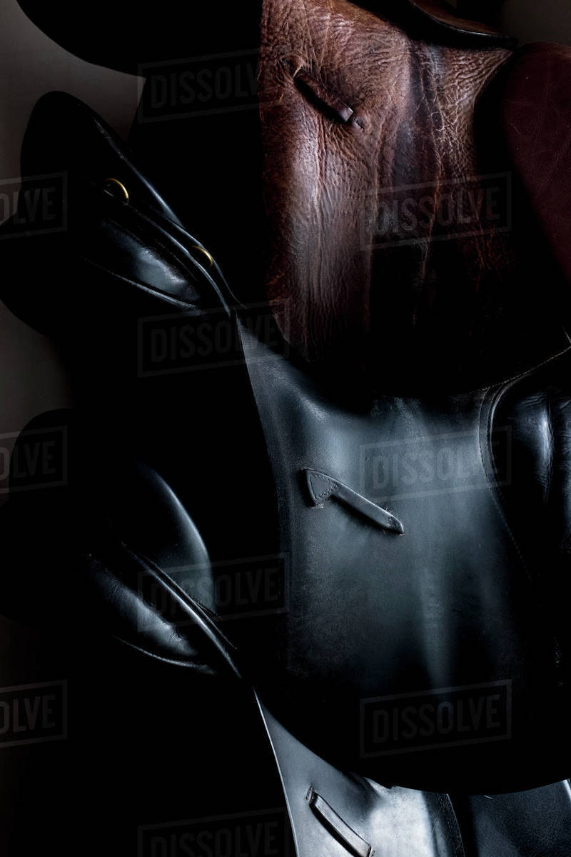 Close up of a selection of black and brown leather saddles. Royalty-free stock photo