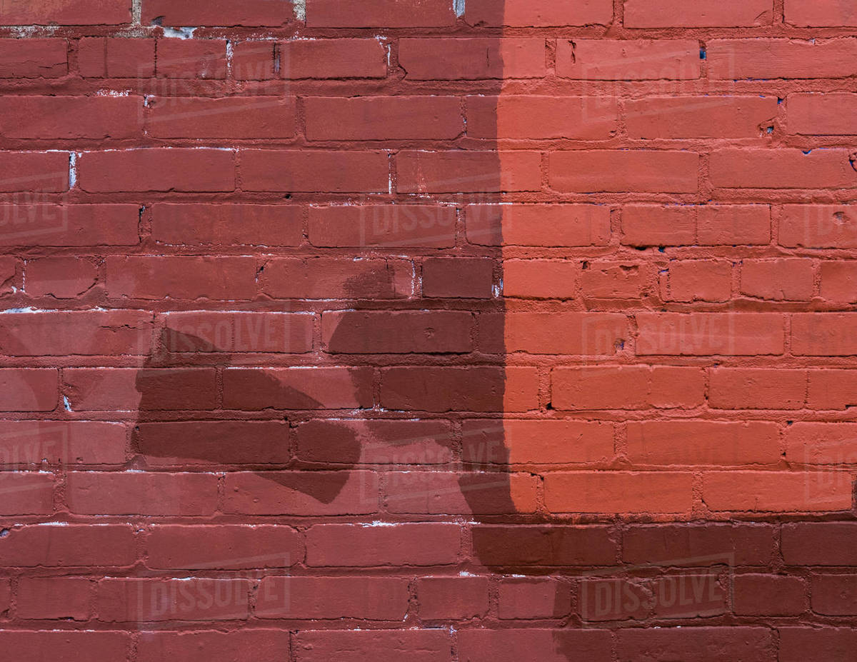 Brown, tan and red paint covering graffiti on old brick wall Royalty-free stock photo