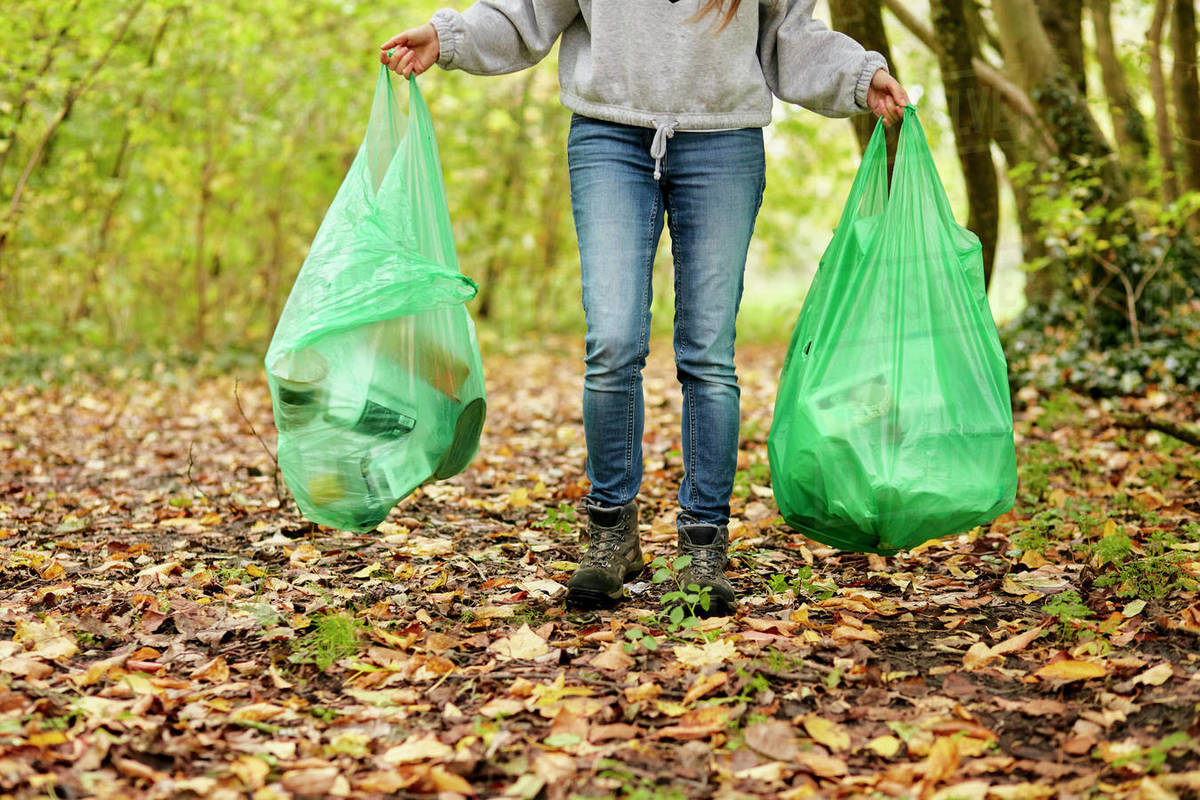 Woman walking in woodland holding two plastic bags full of rubbish Royalty-free stock photo