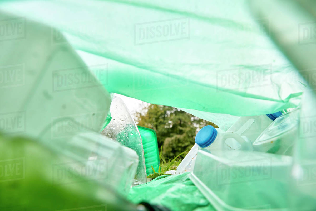View from inside a plastic bag lying on the grass filled with plastic rubbish Royalty-free stock photo
