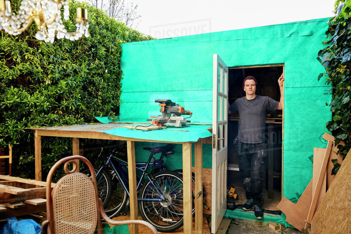 Portrait of man standing in doorway of garden shed used for carpentry Royalty-free stock photo